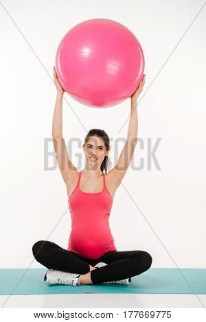 Beautiful pregnant woman doing exercises with fitball over white background