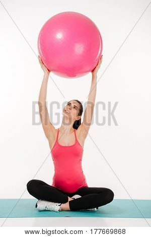 Portrait of a pregnant woman exercising with yoga ball sitting on mat isolated on white background
