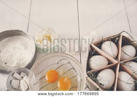 Baking background. Cooking ingredients for dough and pastry, eggs yolks, flour and cookie cutter on white rustic wood. Copy space, mockup for menu, recipe or culinary classes.