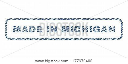 Made In Michigan text textile seal stamp watermark. Blue jeans fabric vectorized texture. Vector caption inside rounded rectangular banner. Rubber sign with fiber textile structure.