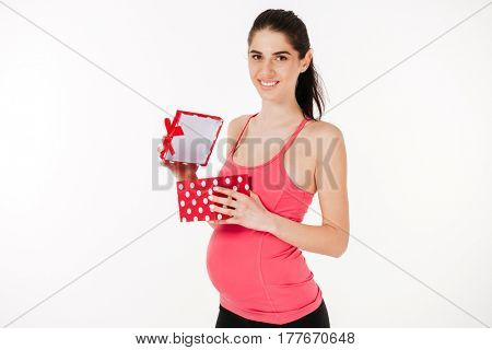 Happy young pregnant woman standing and holding opened gift box isolated on white background