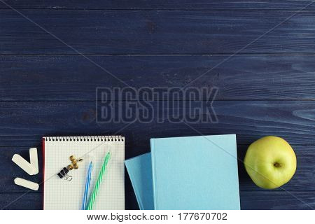Books and stationery on wooden background