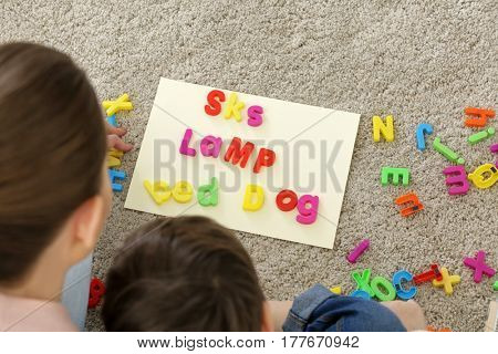 Speech therapist and child composing words of letters in office