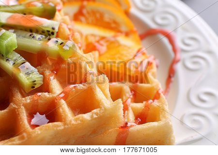 Tasty waffles with delicious fruits and syrup on white plate, close up