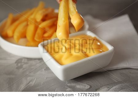 Dipping tasty fries into cheese sauce in bowl, closeup