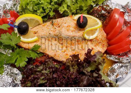 freshly cooked fish and fresh vegetables on the plate. Close-up view from above.