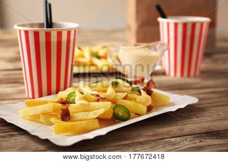 Tasty cheese fries and cups of soda water on wooden table