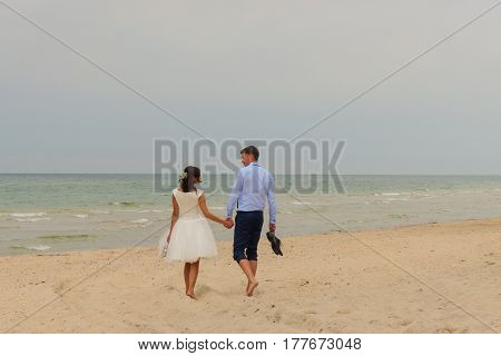 Beautiful Bride And Groom Walking Together On The Beach