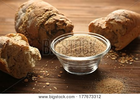Glass bowl of bread crumbs on wooden table