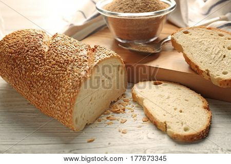 Sliced loaf and glass bowl of bread crumbs on wooden table