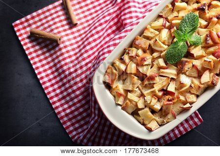 Tasty bread pudding with apples in baking dish on table