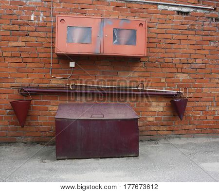 buckets hooks metal box with sand near red brick wall all these items were used for extinguishing fire 100 years ago.