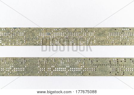 Strips of old punched tape on white surface