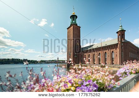 View on city hall (stadshuset) building in Stockholm Sweden Scandinavia Europe. Foreground with flowers and blue cloudy sky as background.