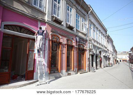 Novi Sad, Serbia: march 1. 2017 - Man painting the walls in Old town in Novi Sad - Serbia