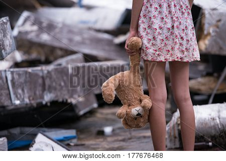 Photo of Sad woman standing and holding bear doll in her hand