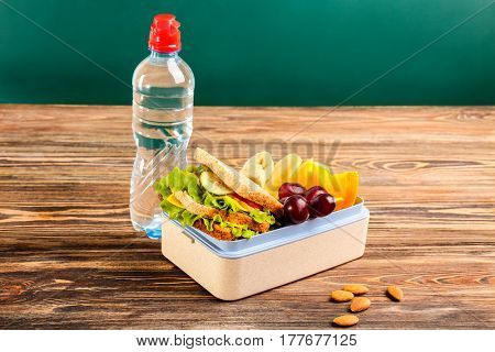 Appetizing food in lunch box and bottle of water on wooden table against chalkboard background