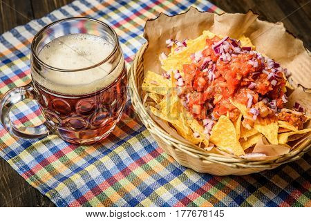 Crispy nachos with tomatoes and red onion served in straw bowl with glass of beer.