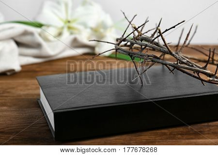 Bible and crown of thorns on wooden table