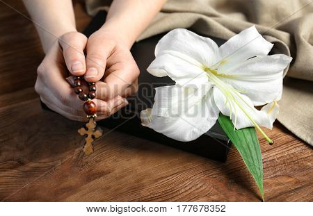 Female hands holding rosary. Lily, Bible and bagging on wooden background