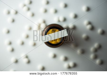White medicine tablets or pills scattered on a white table and  brown glass medicine bottle on center, with blank paper on top for your own message. Intentionally shot with high contrast shadows.