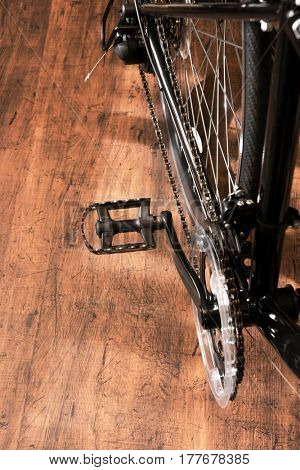 Road bike or racing type bicycle, on a wooden floor of a cycle workshop. Focus on pedal, shallow depth of field.