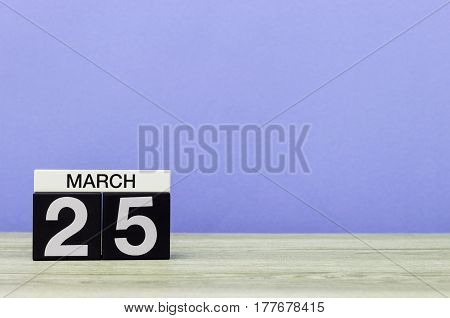 March 25th. Day 25 of month, calendar on table with purple background. Spring time, empty space for text