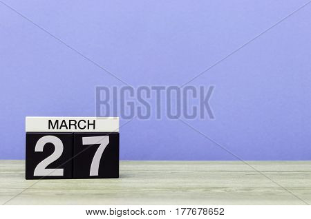 March 27th. Day 27 of month, calendar on table with purple background. Spring time, empty space for text. World Theatre Days.
