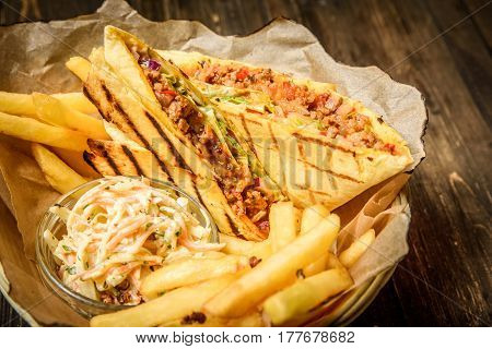 Close up shot of burritos served with French fries and cole slaw.