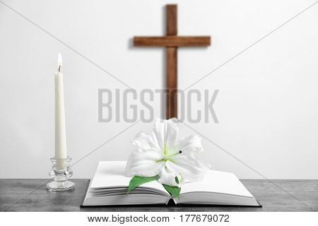 Composition with Holy Bible, lily, candle and cross on light background