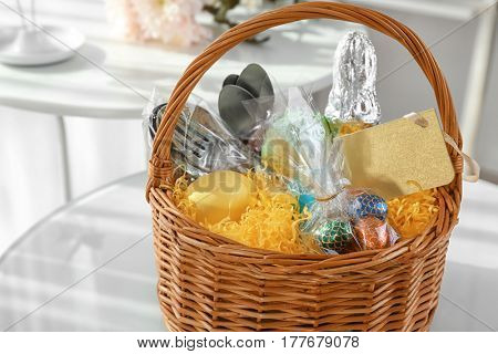 Easter basket with presents and flatware on white table