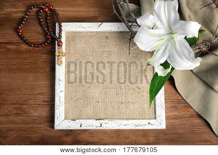 Composition with frame, bagging, rosary, crown of thorns and lily on wooden background