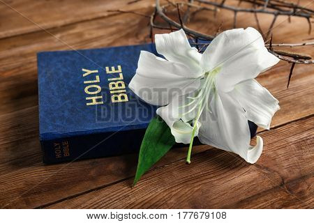 Composition with Holy Bible, crown of thorns and white lily on wooden background