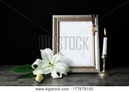 Frame, candle and Easter white lily on table