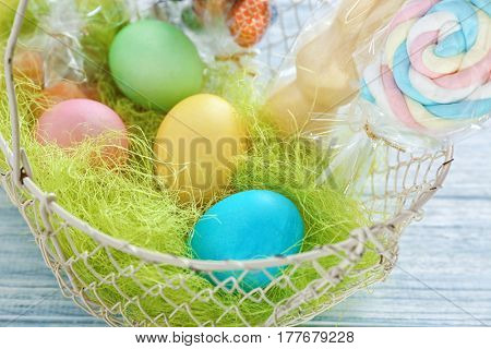 Easter basket with eggs and candies on wooden table