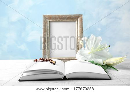 Composition with photo frame, lily, rosary and opened book on light background