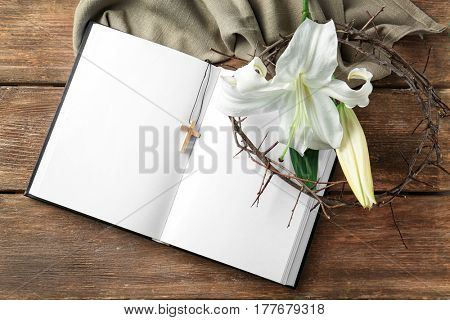Holy Bible, crown of thorns and Easter white lily on wooden background