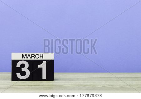March 31st. Day 31 of month, wooden calendar on purple background. Spring time, empty space for text.