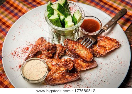 White plate with chicken wings served with sauces and cucumber.