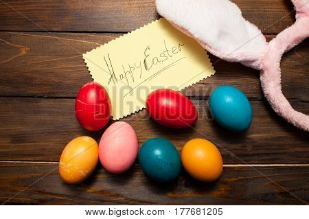 Pink Bunny Ears With Easter, Colored Eggs And The Words Happy Easter On Yellow Piece Of Paper On The