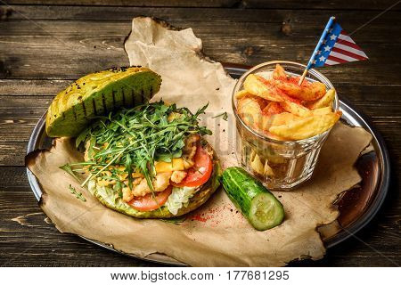 Grilled hamburger with ruccola served with glass of potato wedges with small America flag thrust in it.