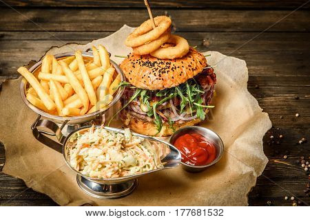 Wonderfully looking hamburger served with French fries, sauce and cole slaw.
