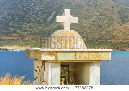 Wayside chapel made of light marble with a stone cross. In the chapel of installed icons candles and incense. On the background of sea and mountain. Village Bali Crete island Greece