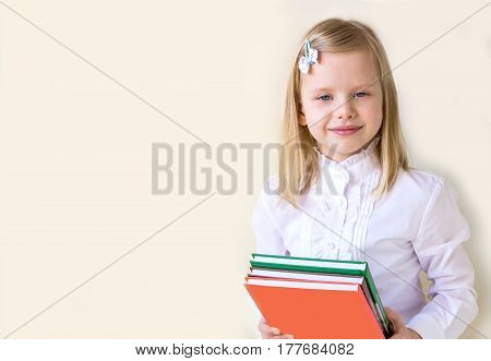 Smart cute school-age child with books on the solid background.