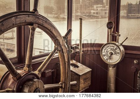 steering wheel and engine controls (telegraph) on a vintage ship bridge, retro sepia toning