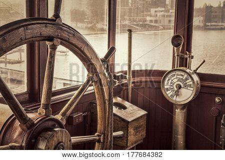 steering wheel and engine controls (telegraph) on a vintage ship bridge, retro sepia toning