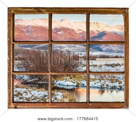 dusk over Canadian River and Medicine Bow Mountains in North Park near Walden, Colorado as seen  through vintage, grunge, sash window with dirty glass