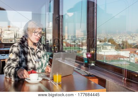 Female Freelancer working on Computer Laptop developing network Project sitting at wooden Table inside roof top Cafe with City View throw the Window