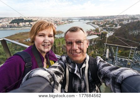 Smiling Man and Woman taking self Portrait at scenic view spot of large city