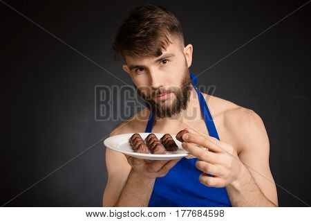 A special gift to woman. Chocolate made with lve for woman all over the world. Naked smiling man isolated on grey background with candies sweet-stuff Bonjour.